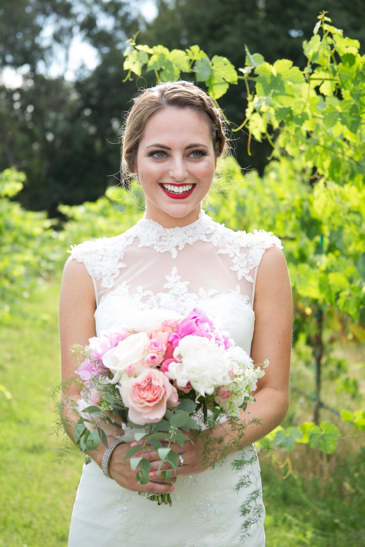 beautiful bride holds summer flower bouquet at her vintage inspired winery wedding in northern california