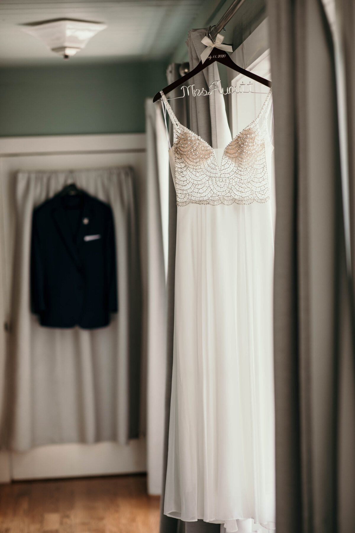 An image of the bride's beautiful wedding dress hanging on a wire name hanger at a window with the sun lighting up the beaded bodice and soft folds in the long dress by Garry & Stacy Photography Co - Bradenton Florida wedding photography