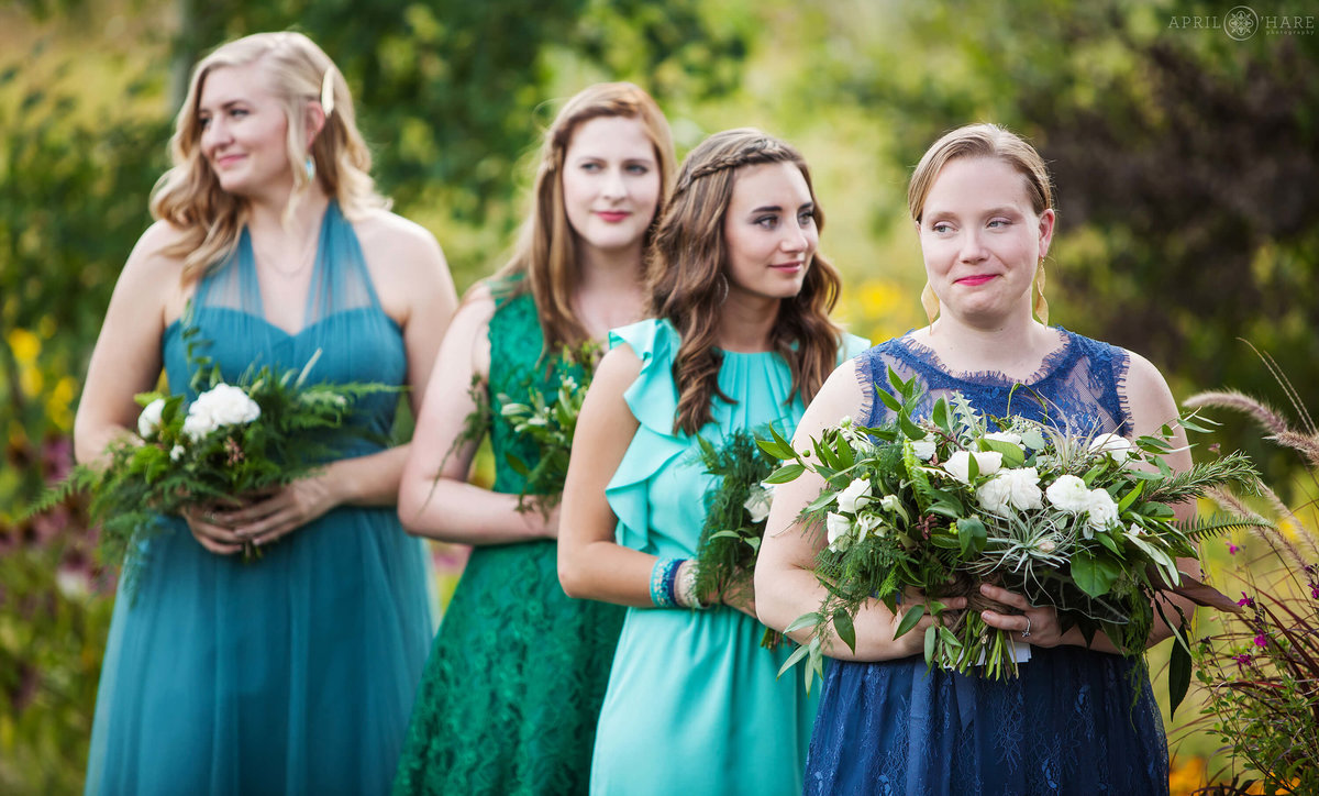 Bridesmaids in shades of blue and green at outdoor Colorado wedding Denver Botanic Gardens Chatfield Farms