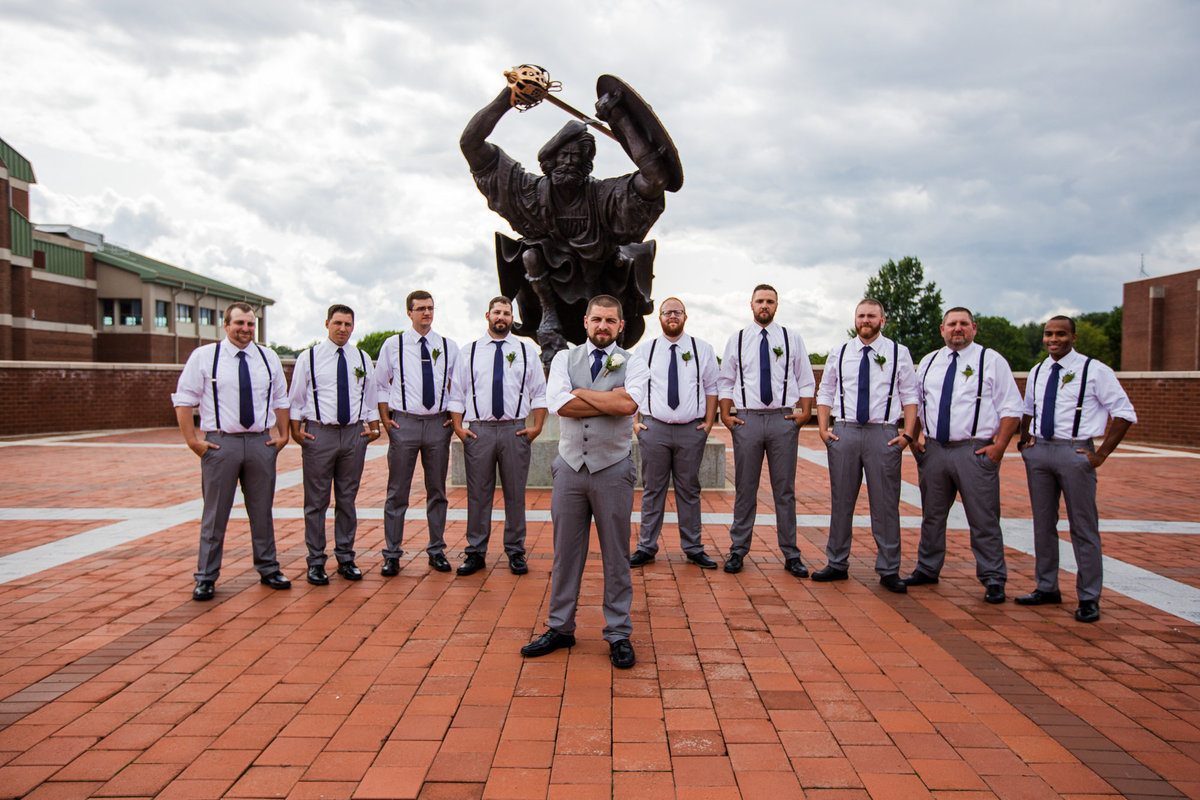 Groom and groomsmen pose in front of Angus statue on the campus of Edinboro University
