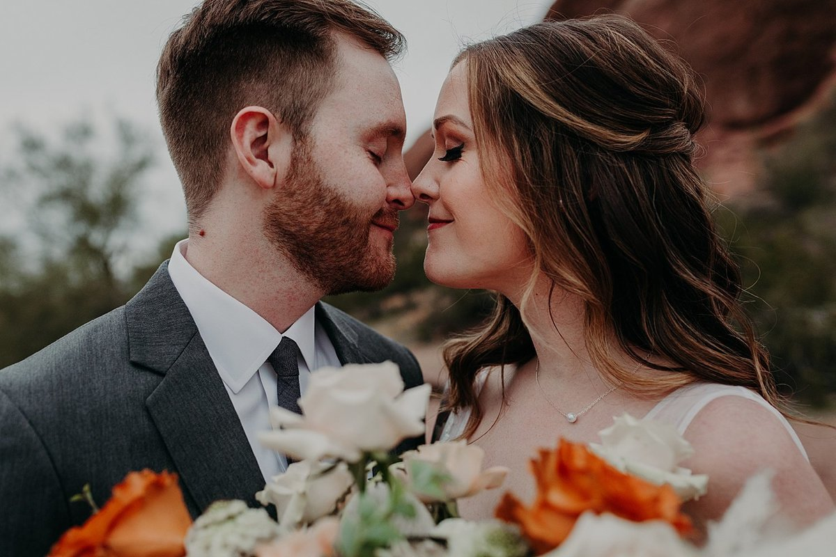 Bride and groom nuzzle noses as they hold the bouquet together