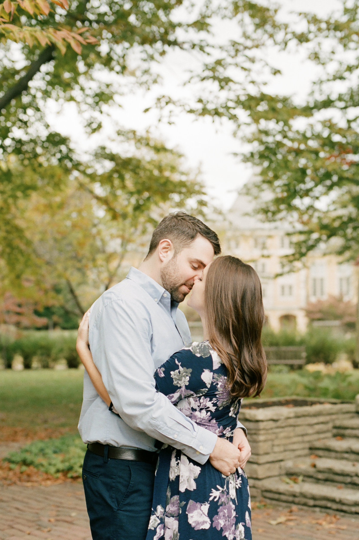 couple hugging with trees and colonial buildings in background
