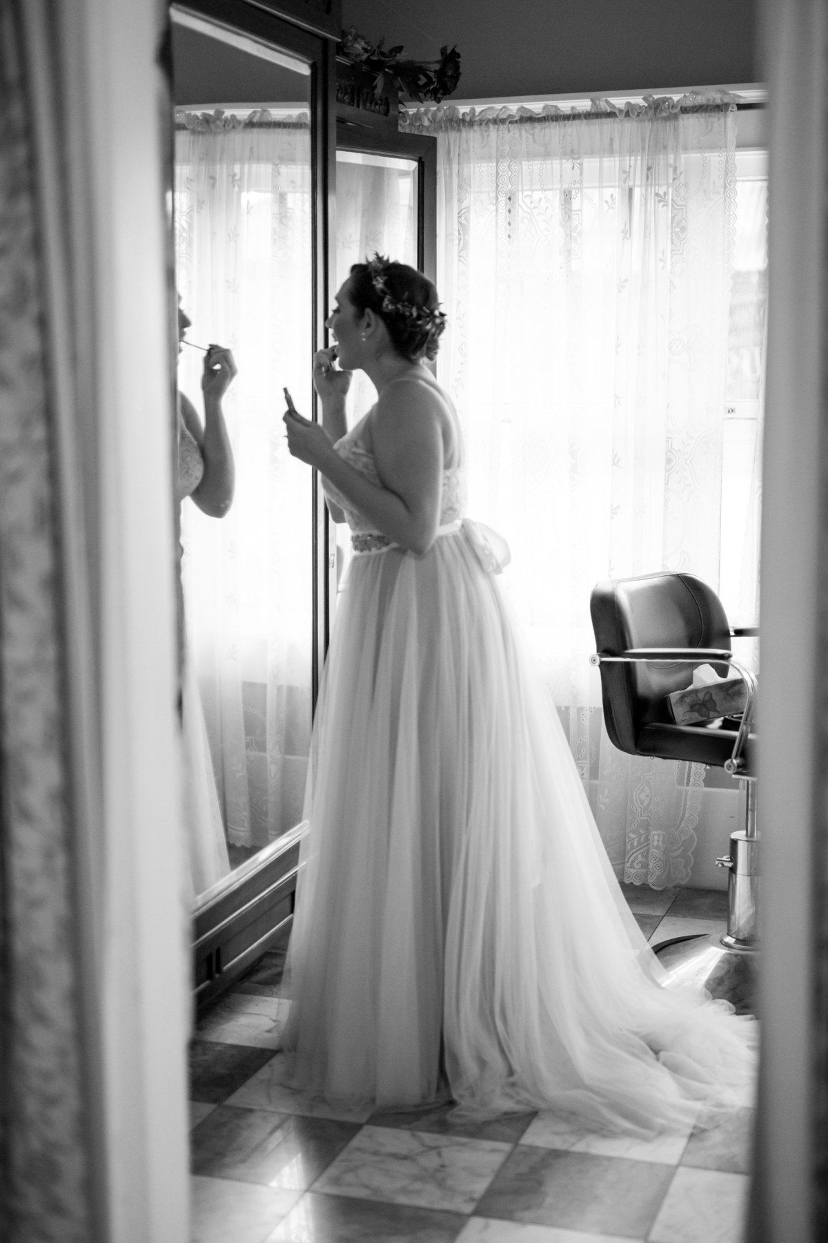 black and white portrait of bride putting make up on getting ready before ceremony at Spinelli's wedding venue Hill Country