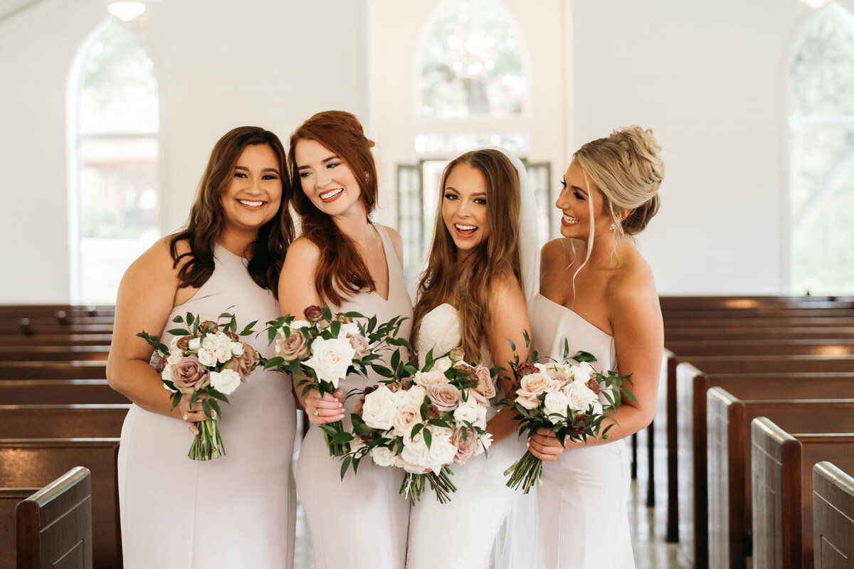 Bride and bridesmaids in church holding white bouquets