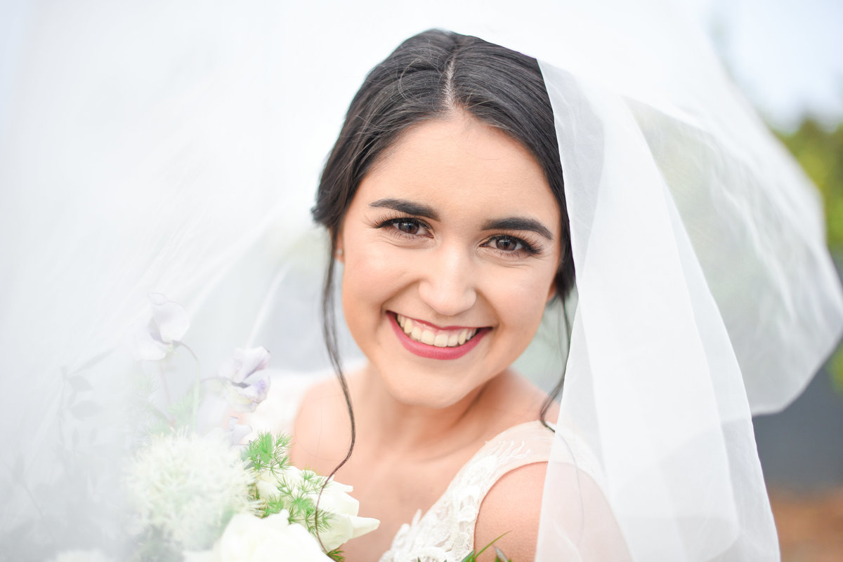 bride smiles at camera with veil over her head