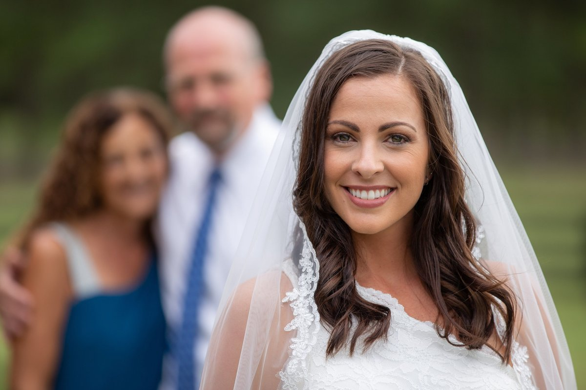 bride standing in front of mom and dad