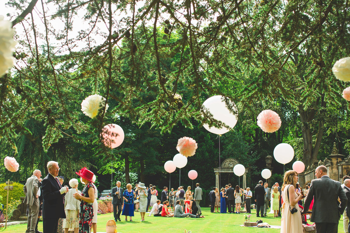 drinks reception on the lawn at thornbridge hall with picnic baskets and blankets. big balloons and pom poms
