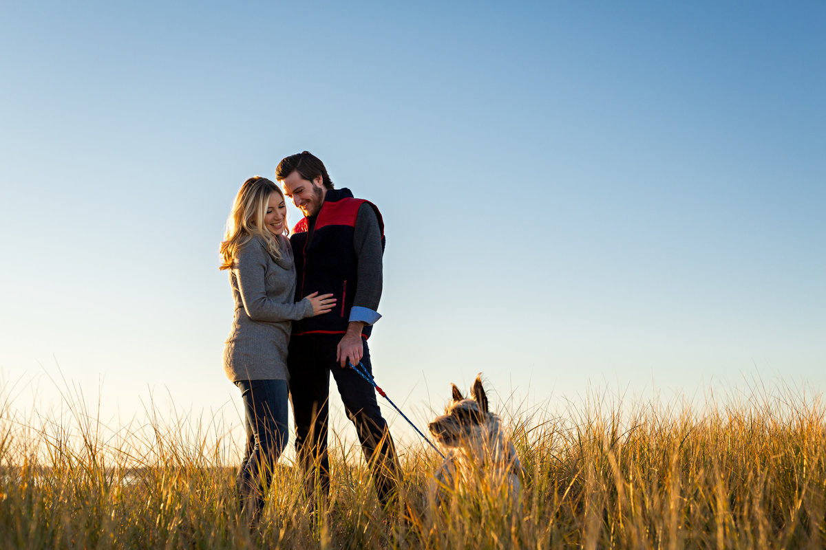 Plum Island MA Wedding Photographer the engaged couple hold onto each other and laugh as their puppy steals the show on their engagement session
