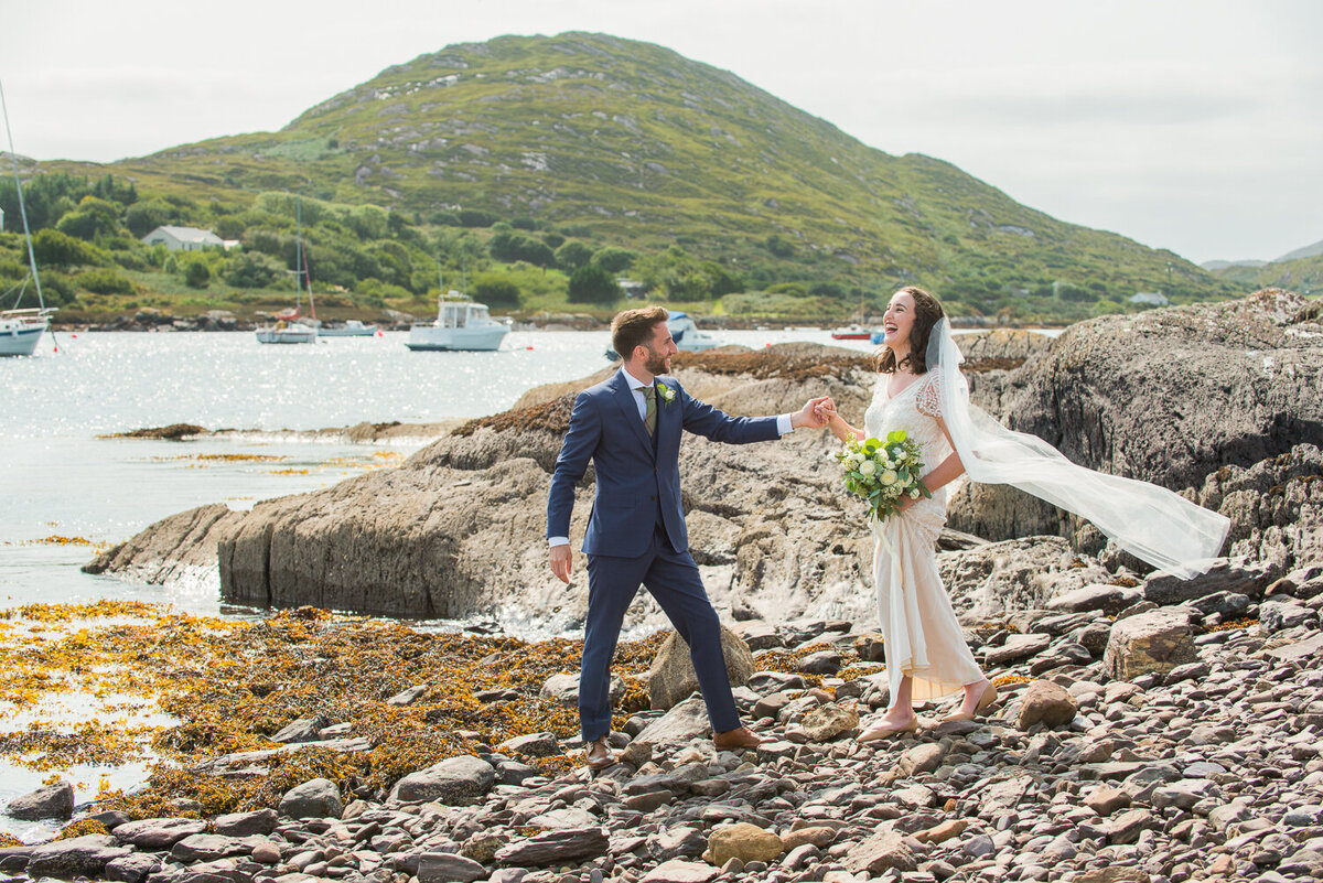 Bride wearing sequenced, vintage wedding dress and veil standing on pebbled beach laughing with groom wearing a navy suit and green, tweed tie