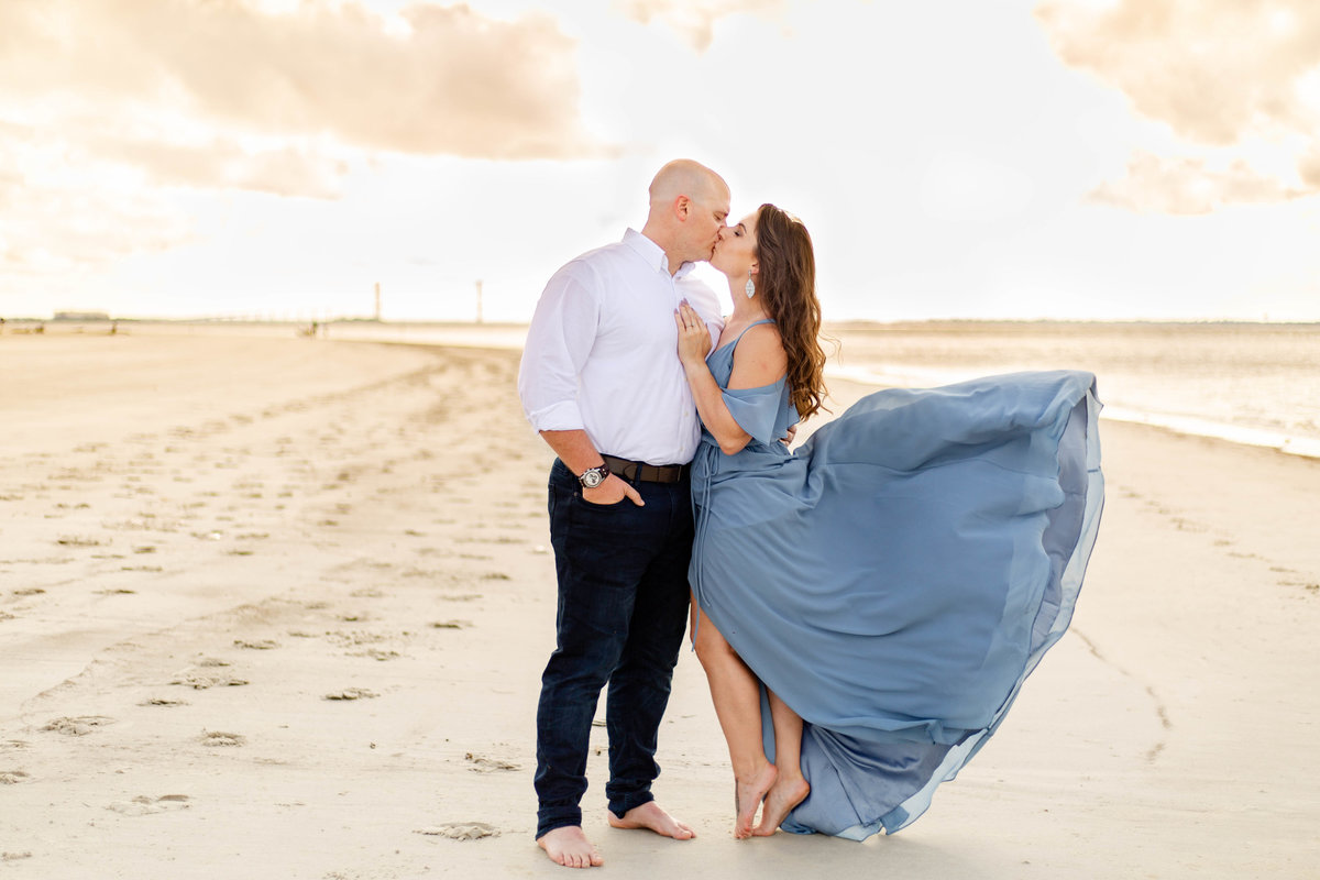 Couple at beach engagement session Jekyll Island in Georgia as her blue dress flows in the wind