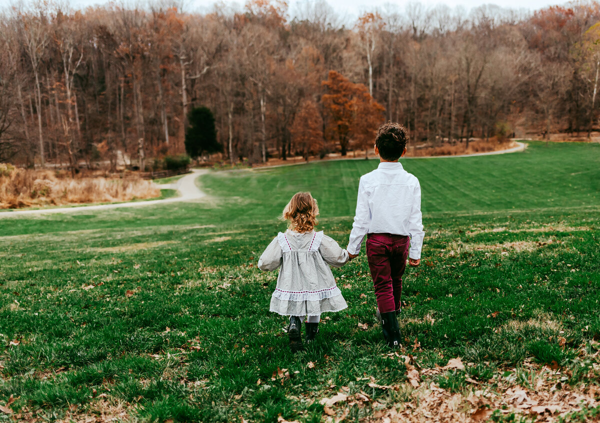 Boy and girl holding hands and walking towards the woods