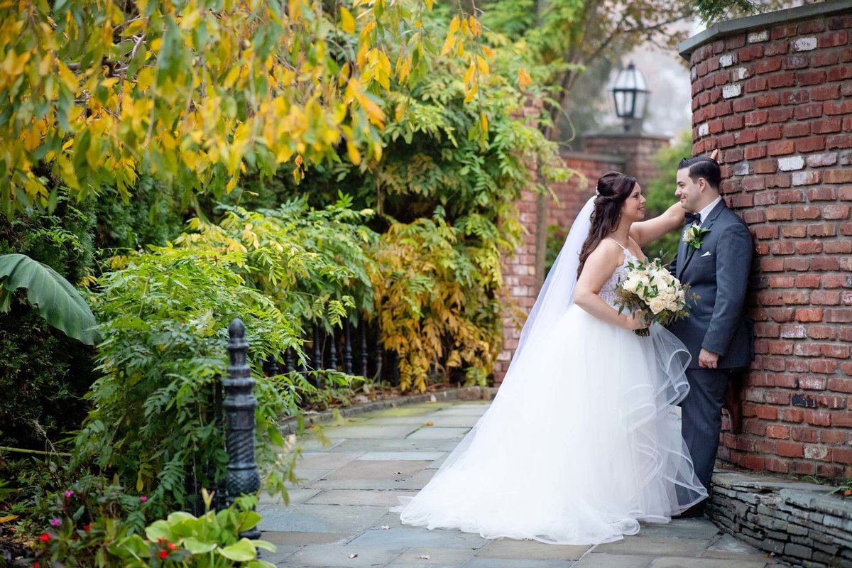 Bride and groom against the brick wall at Fox Hollow