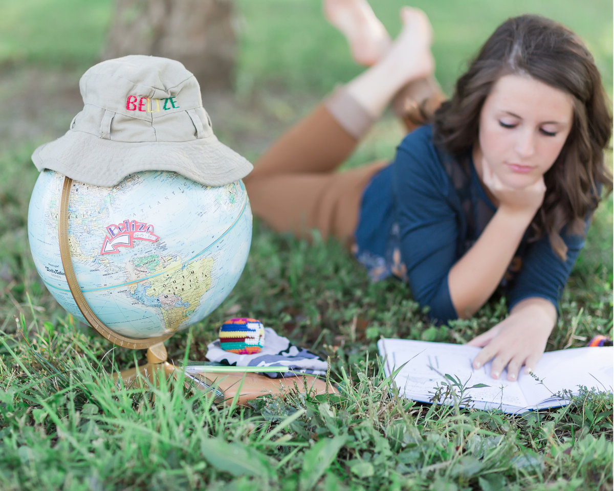 Senior girl-mission trip memorabilia-globe-hat-journal-laying down