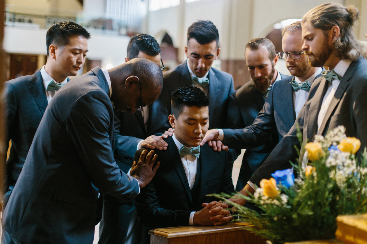 Groomsmen praying at Catholic wedding