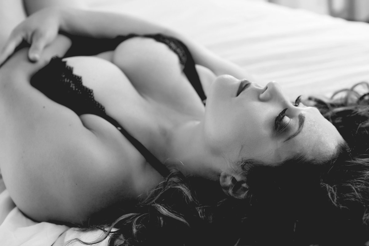 close up of female laying on her back with eyes closed wearing sexy black lingerie