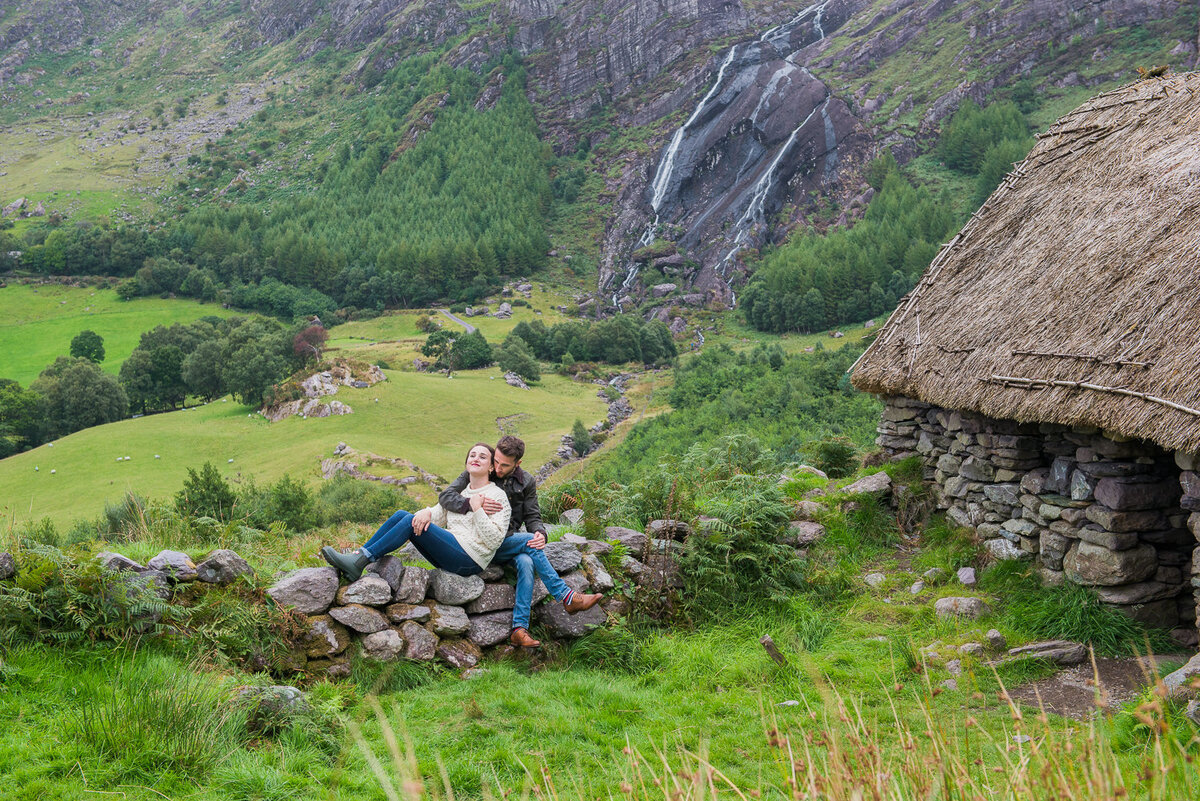 young couple in country dress relaxing on a stone wall beside an Irish thatched cottage with a waterfall in the background