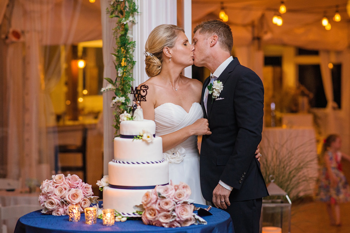 Bride and groom kissing next to the wedding cake