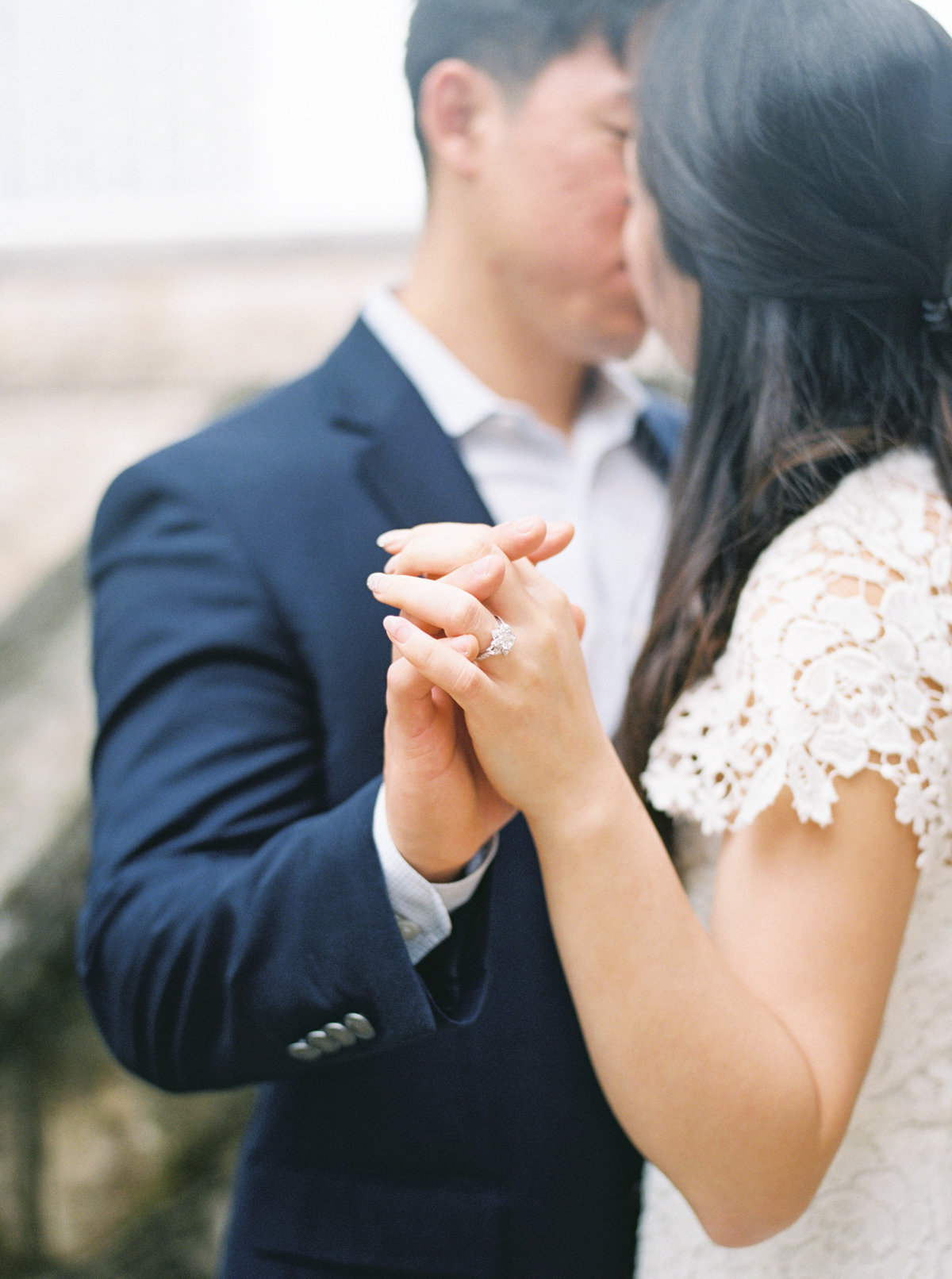 Couple kiss while locking fingers -ring photo- engagement photo