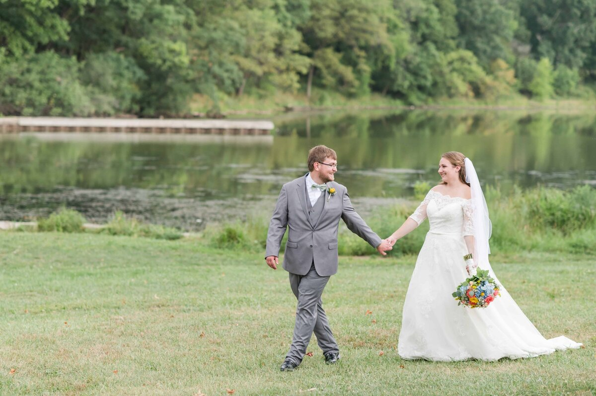 Groom leading his bride in grassy field in Illinois.