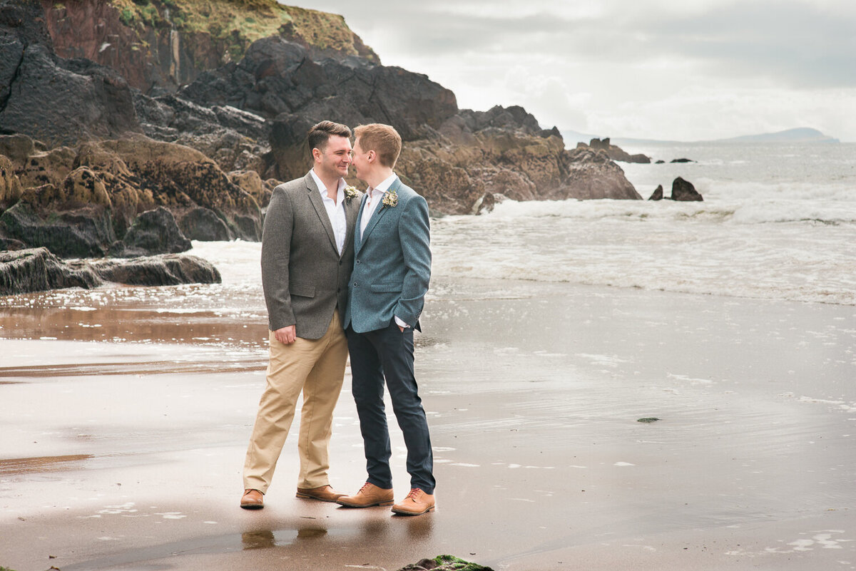 Gay wedding grooms kissing on the beach