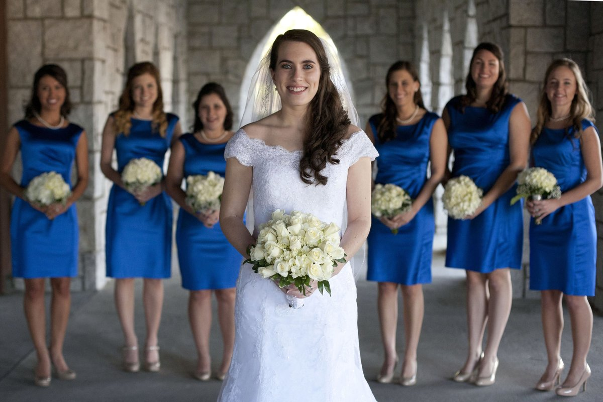 bride standing in front of bridesmaids in royal blue dresses