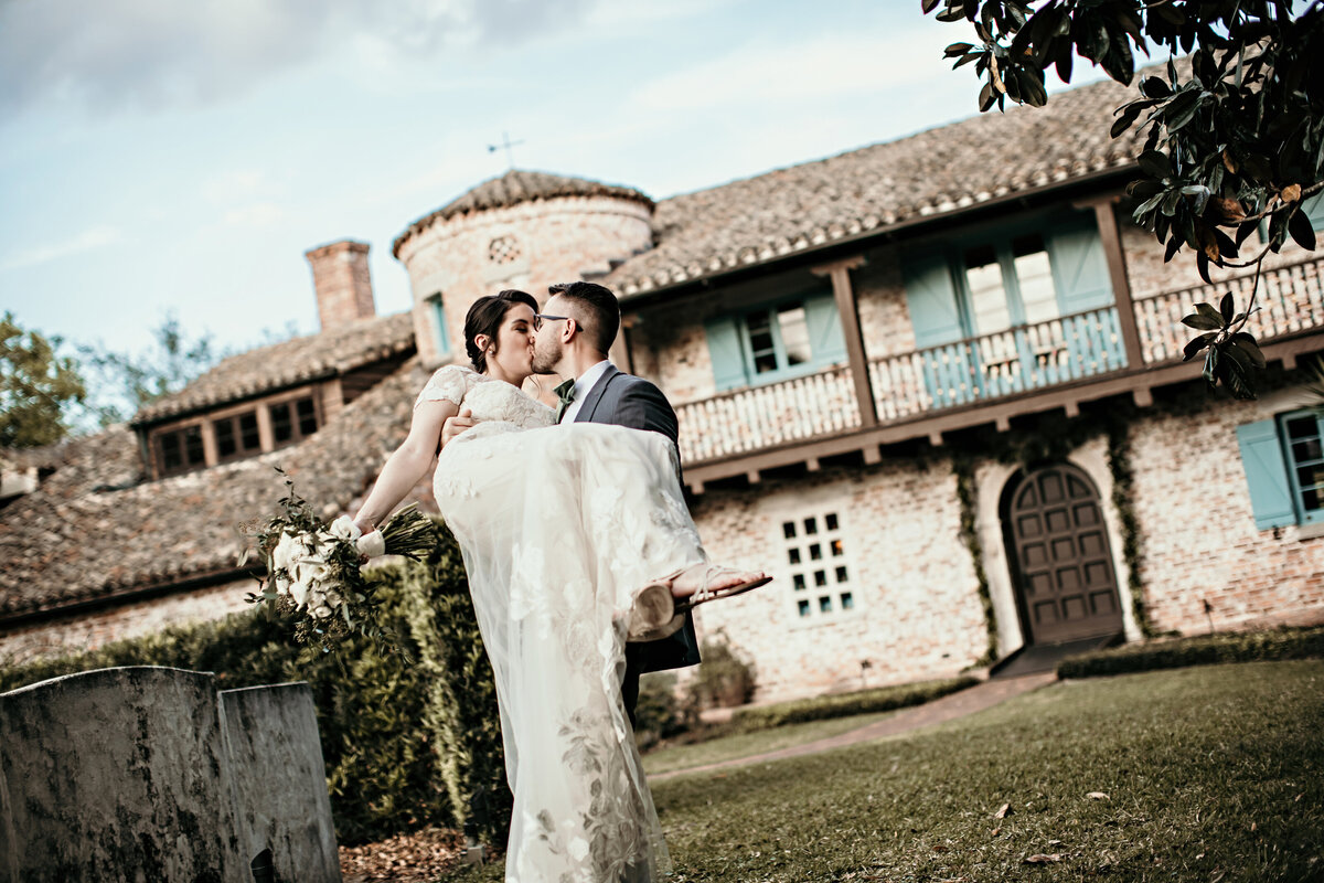 A photograph of a groom holding his bride up in his arms as they kiss while the bride holds her bouquet as they stand in front of their picturesque vintage wedding venue