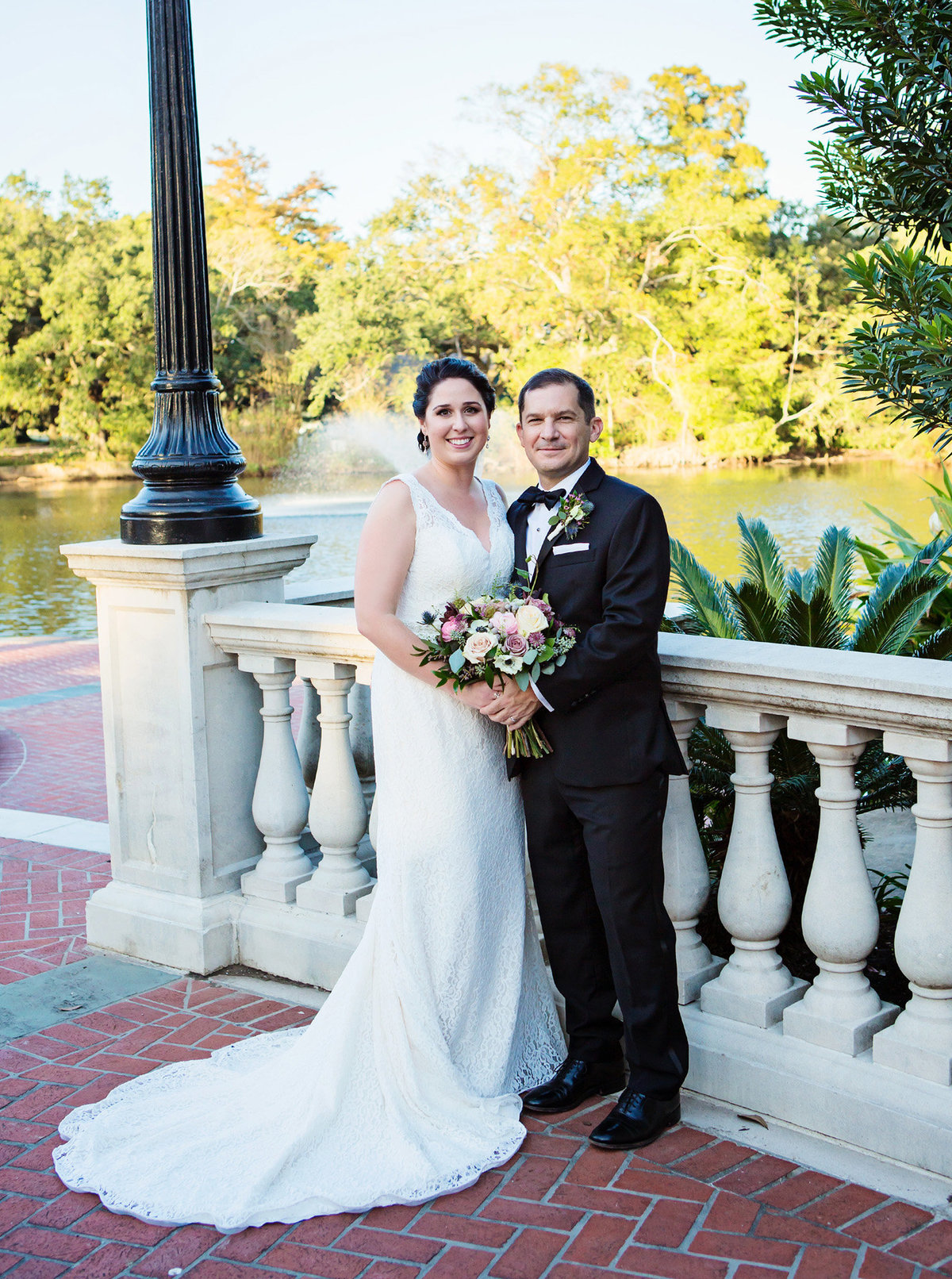 NOLA bride and groom beside cement railing at Newman Bandstand