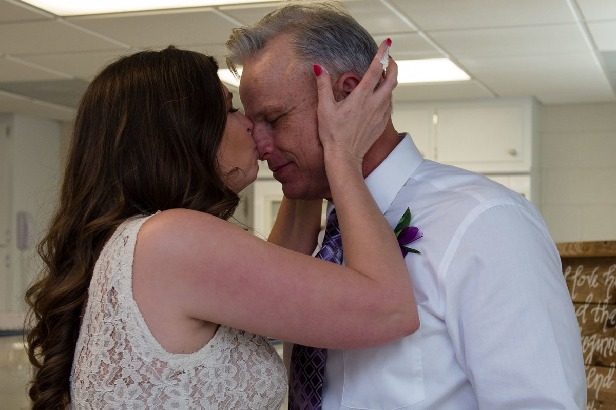 kissing grooms nose with cake on finger