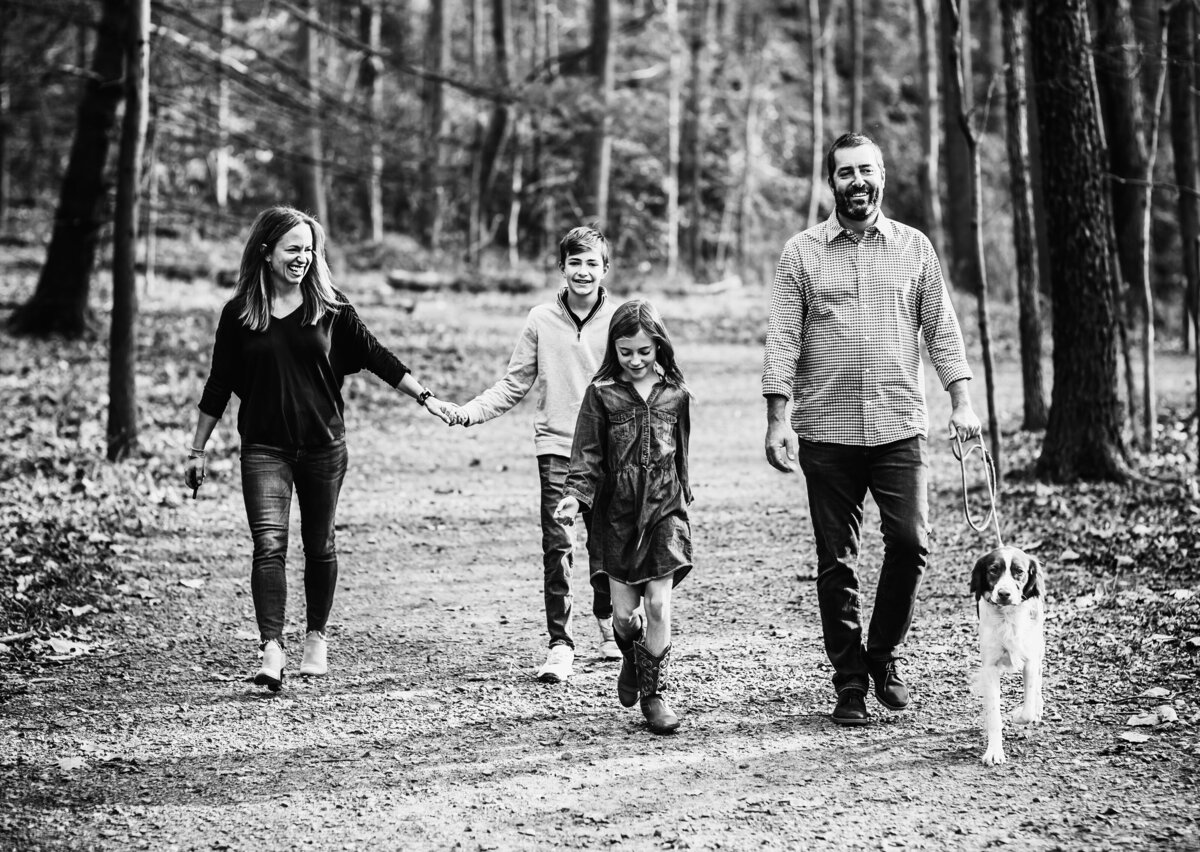 black and white photo of family walking in the woods
