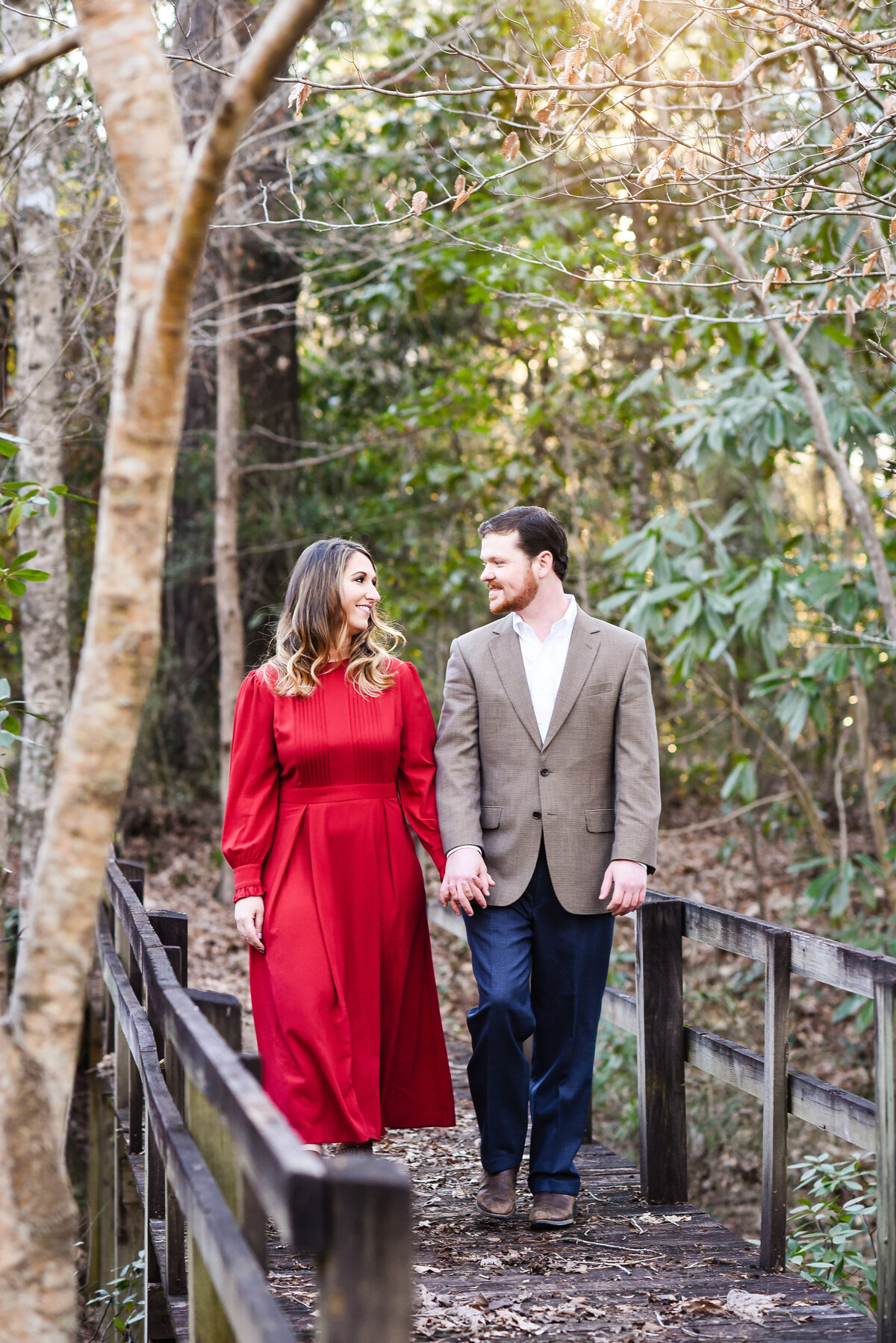 Beautiful Mississippi Engagement Photography: couple walks hand in hand over old bridge at sunset