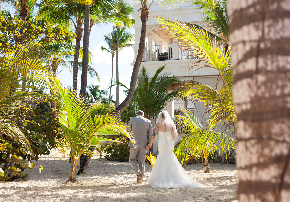 newlyweds walk during processional in tropical punta cana