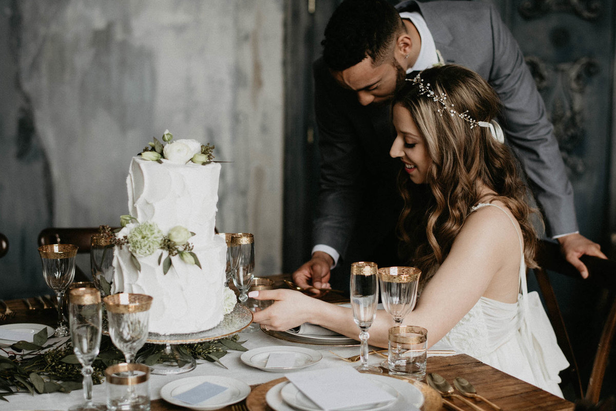 black groom leaning over white bride at harvest table looking at wedding cake