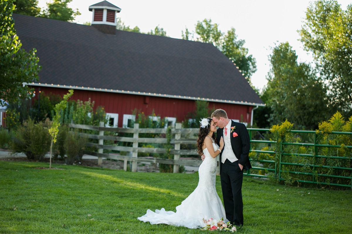 wedding couple in front of big red barn