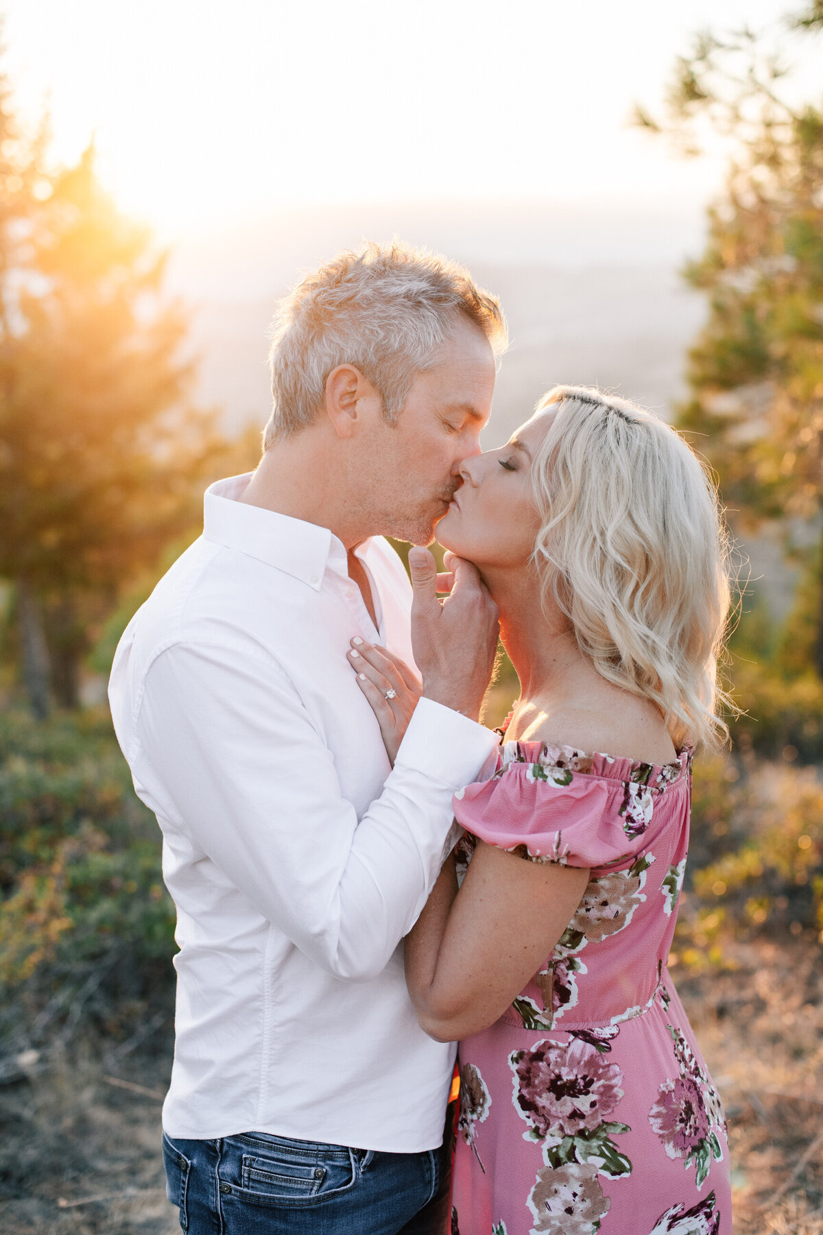 Couple kissing during sunset engagement session on top of Echo Ridge Trail