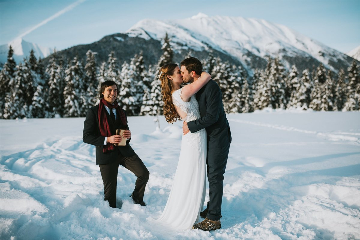 bride and groom first kiss during their winter elopement at moose meadow, with mountain backdrop