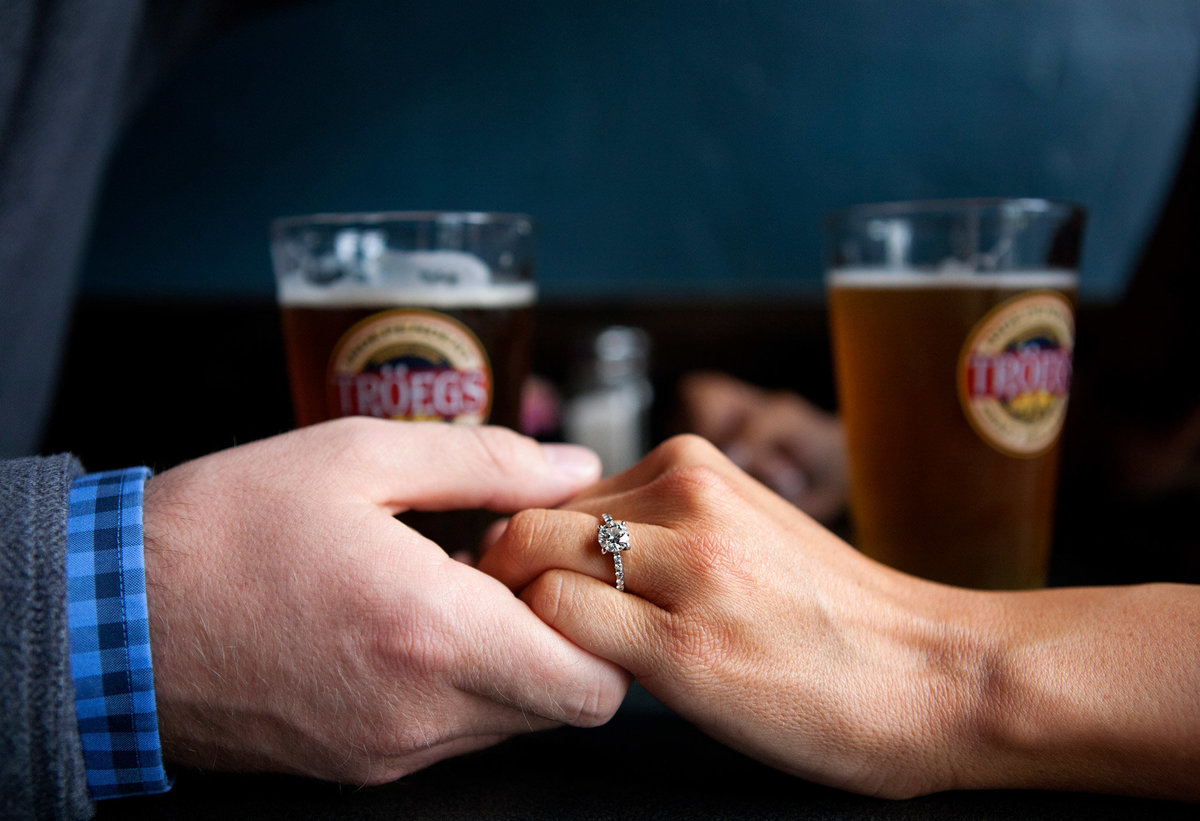 Engaged couple holding hands on table with beer