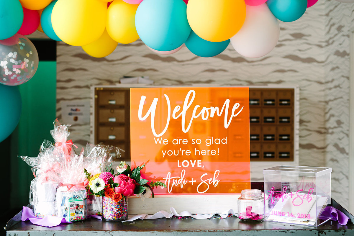 Wedding welcome table with bright orange acrylic welcome sign and balloon garland