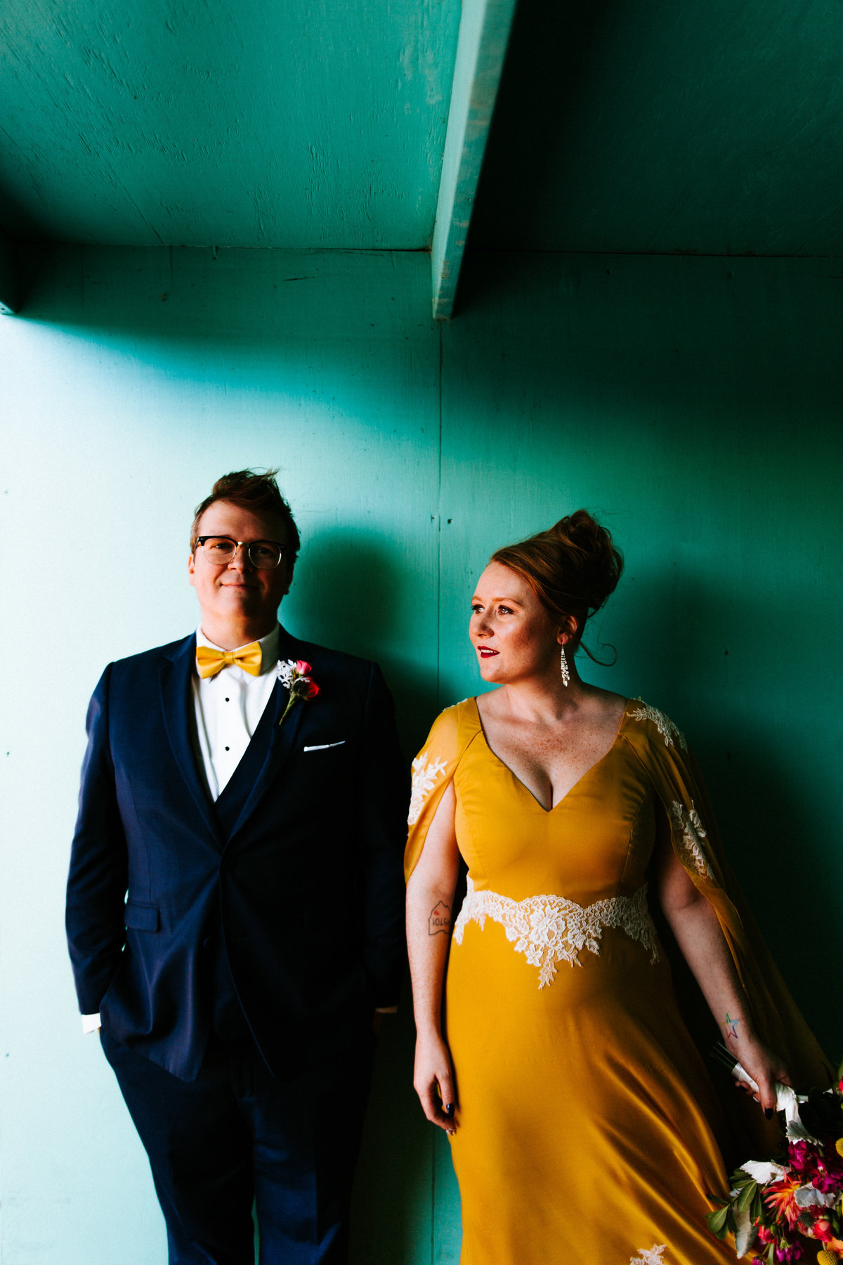 One of the top wedding photos of 2019. Taken by Adore Wedding Photography- Toledo Ohio Wedding Photographers. This photo is of bride and groom in front of a colorful wall at the Toledo Zoo