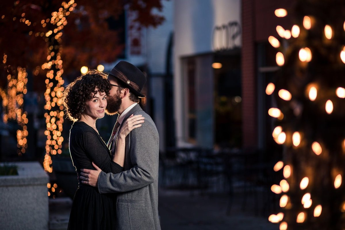 couple kisses for engagement with lights at downtown Decatur Atlanta
