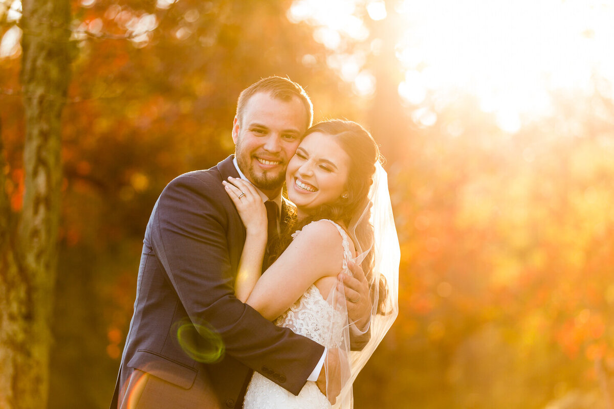 joyful wedding couple during sunset golden hour in the fall