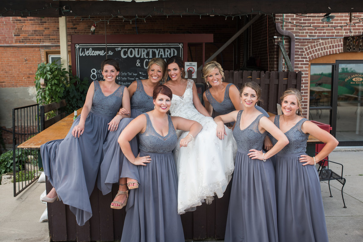 bridesmaides pose for photo with bride outside