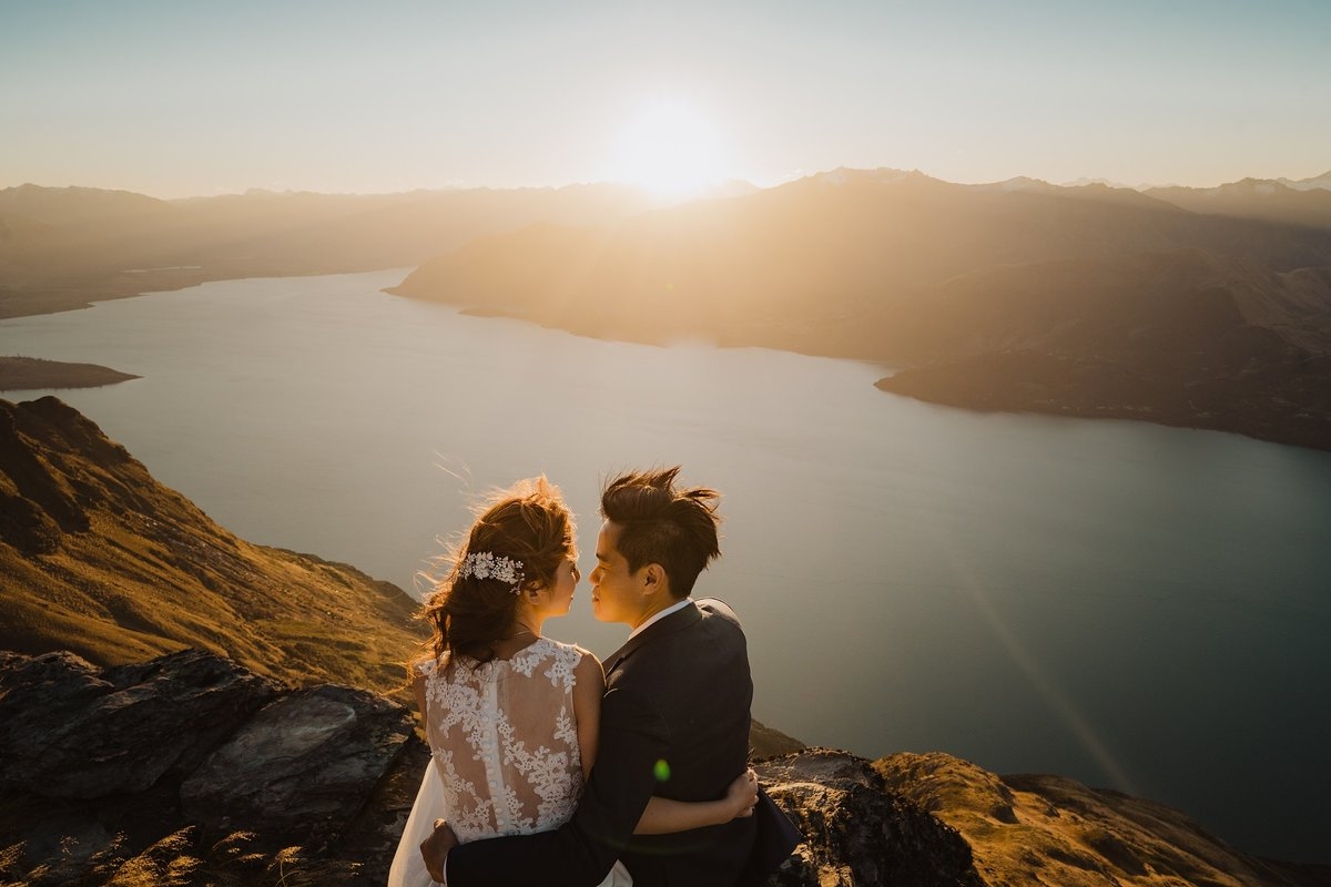 bride and groom sat on a cliff at sunset over the water