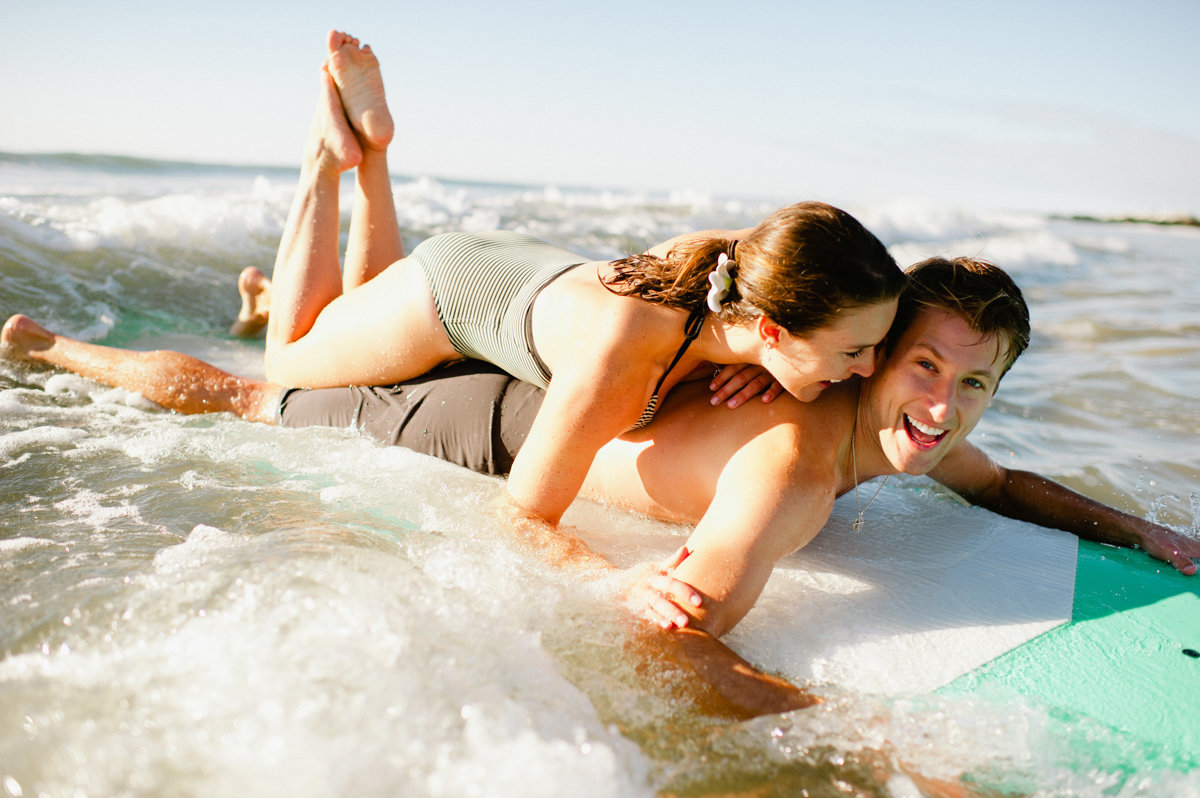 happy couple playing in the surf lifestyle photography