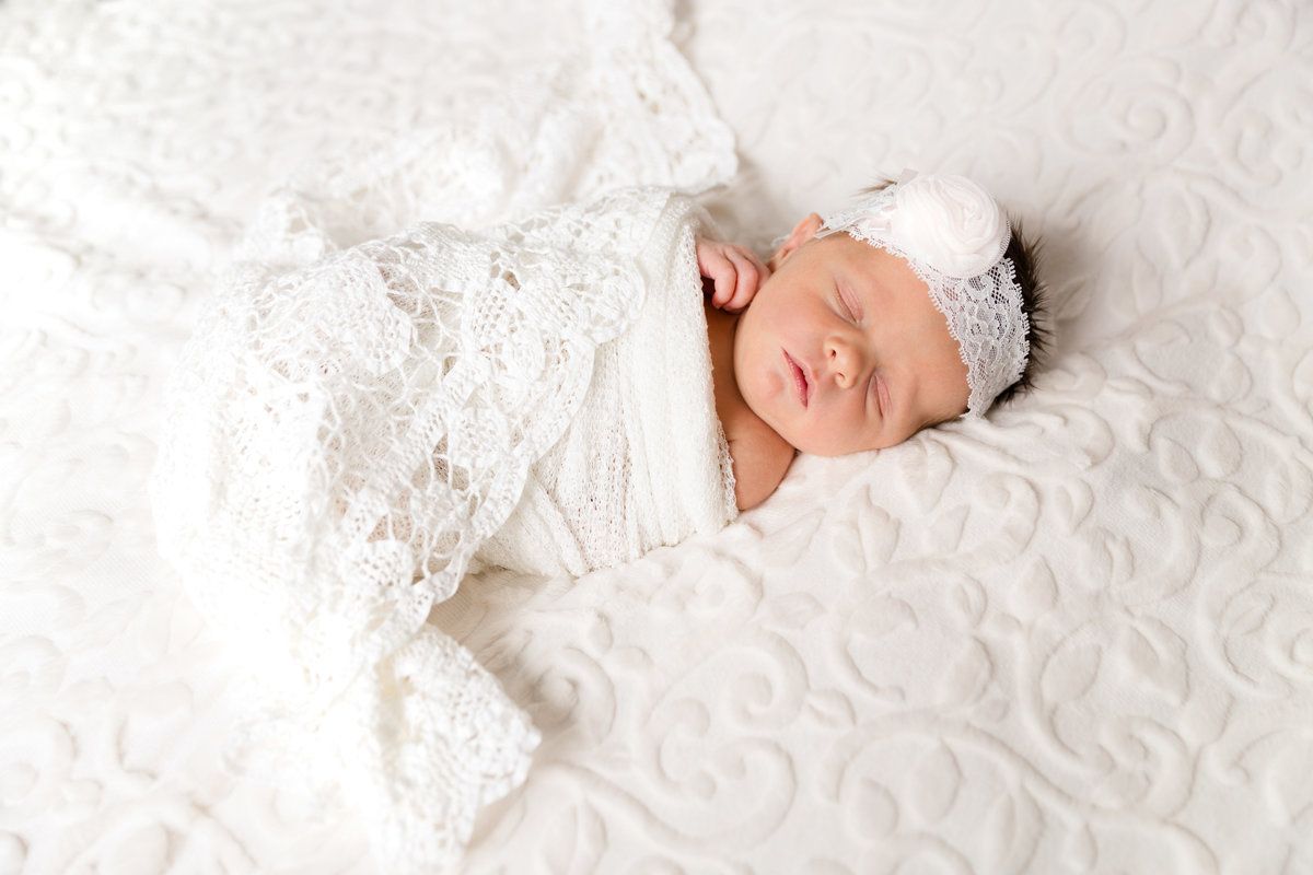 newborn baby swaddled in white blanket laying on a white blanket