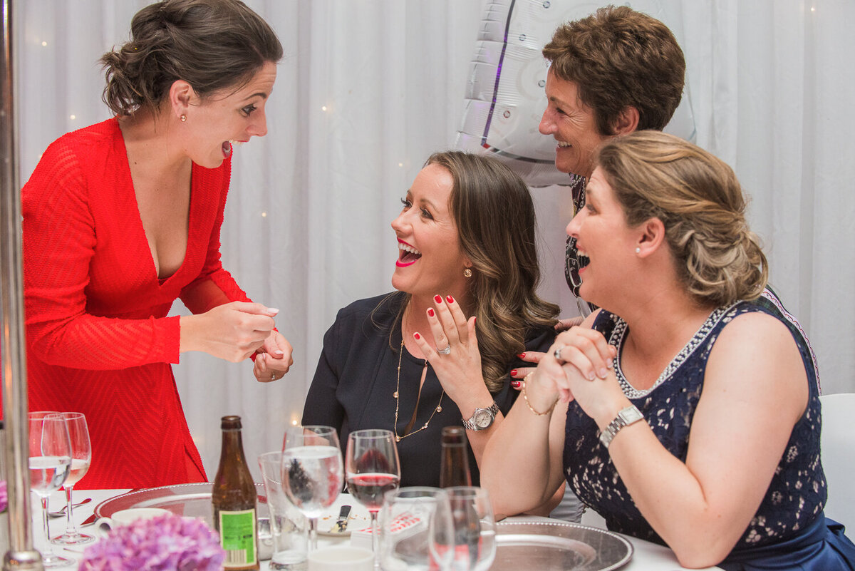 wedding guest in red dress laughing with gay brides at wedding reception