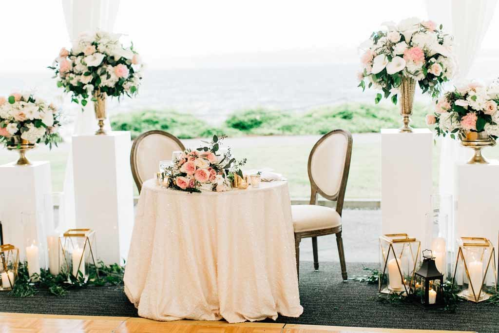 Elegant sweetheart table surrounded by lush floral urns is a major focal point of this outdoor summer tent wedding.