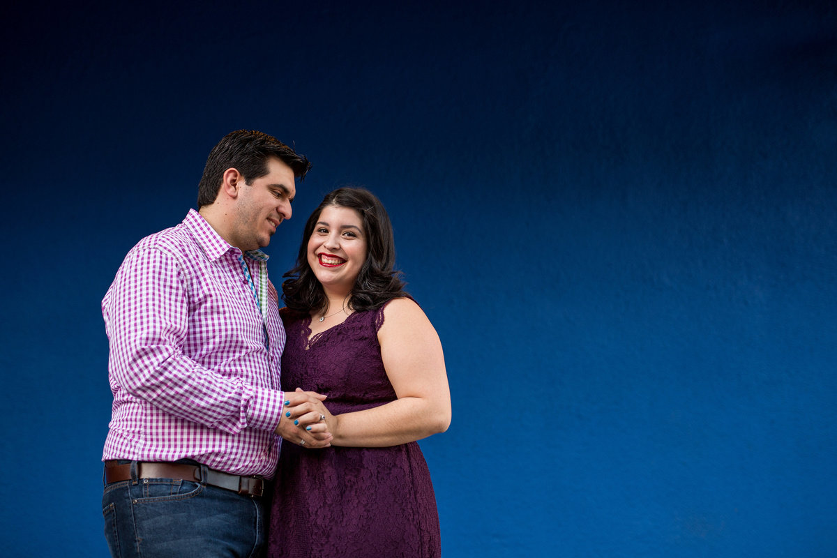 Couple on their engagement session standing in front of a blue wall and holding hands and posing for Expose The Heart Photography.