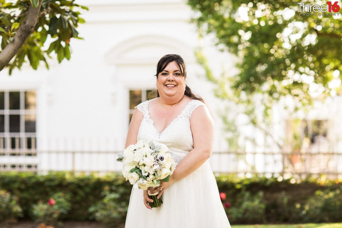 Smiling Bride poses for photos in front of the Richard Nixon Library wedding venue