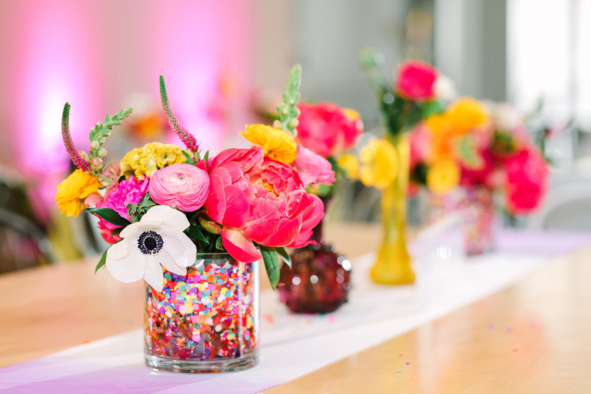 Wedding reception table setting with neon pink and yellow floral centerpieces filled with confetti at the Unique Space LA weddiing