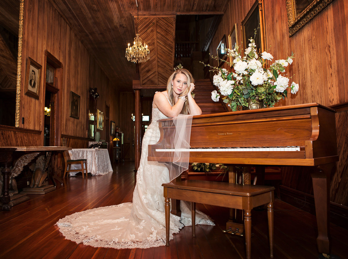 bride leaning on piano in the parlor of Blythewood Plantation